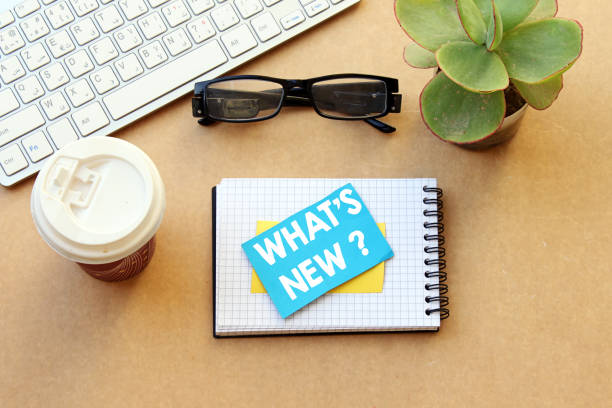 quoi de neuf? concept, bureau: cahier, papier et tasse jetable café, lunettes, clavier, plante en pot - neuf photos et images de collection