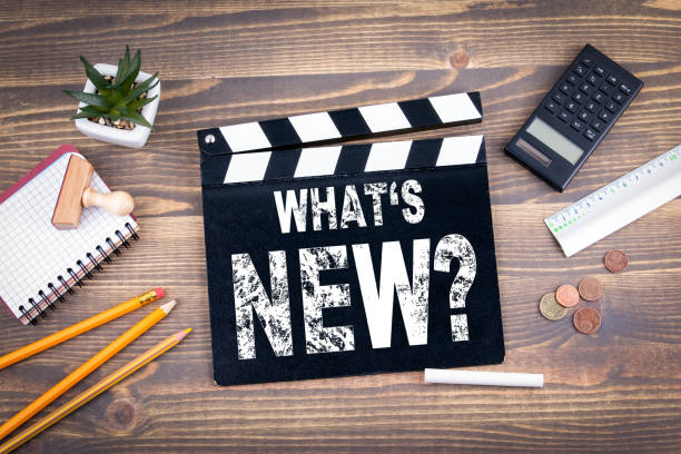 What's New? Movie clapper on a wooden desk stock photo