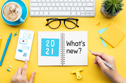 2021 What's new ? or trendy concepts with young person writing text on notepaper and office accessories.Business management,Inspiration concepts ideas