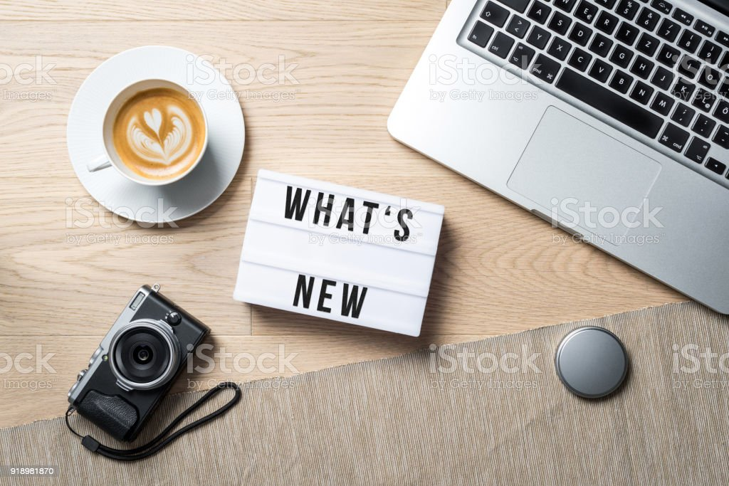 What's new written on lightbox in office as flatlay stock photo