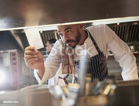 Shot of a chef looking at an order in the kitchenhttp://195.154.178.81/DATA/i_collage/pu/shoots/805551.jpg