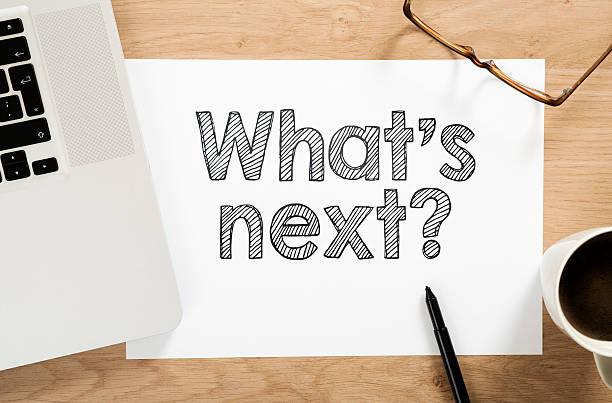 """""""was steht als nächstes an?"""" geschrieben auf papier am schreibtisch - der nächste schritt stock-fotos und bilder"""
