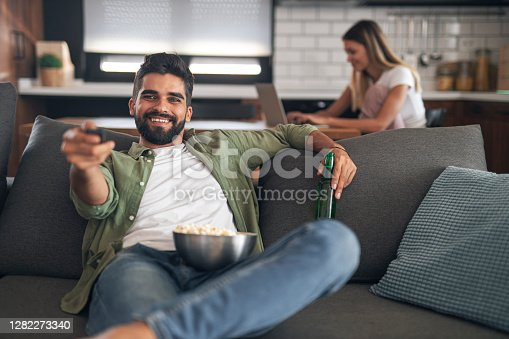 Cheerful handsome man sitting on sofa, eating popcorn, holding remote control and switching channels