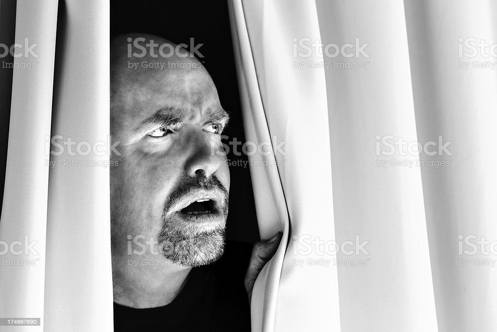 What's that? Nervous man looks out through closed drapes royalty-free stock photo