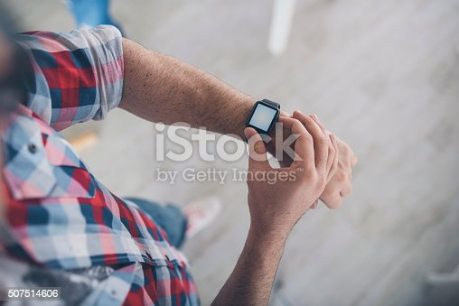 A picture of a young man checking his smart watch