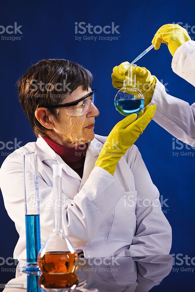 What's this? Senior female scientist examines contents of lab flask stock photo