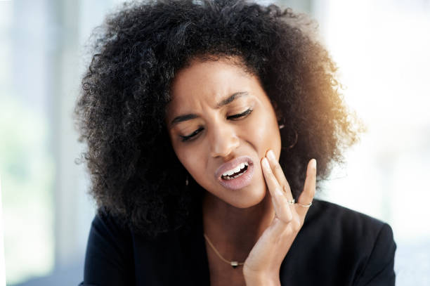 What's wrong with my tooth? Shot of a young businesswoman suffering from toothache at work toothache stock pictures, royalty-free photos & images