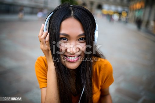Smiling Chinese woman using mobile phone. She is having headphones and looking at the camera