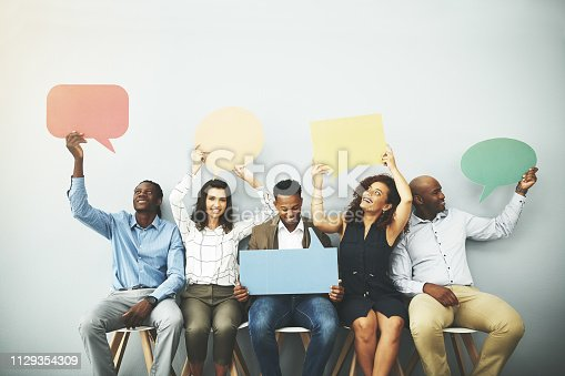 Studio shot of a group of businesspeople holding colorful speech bubbles in line against a gray background
