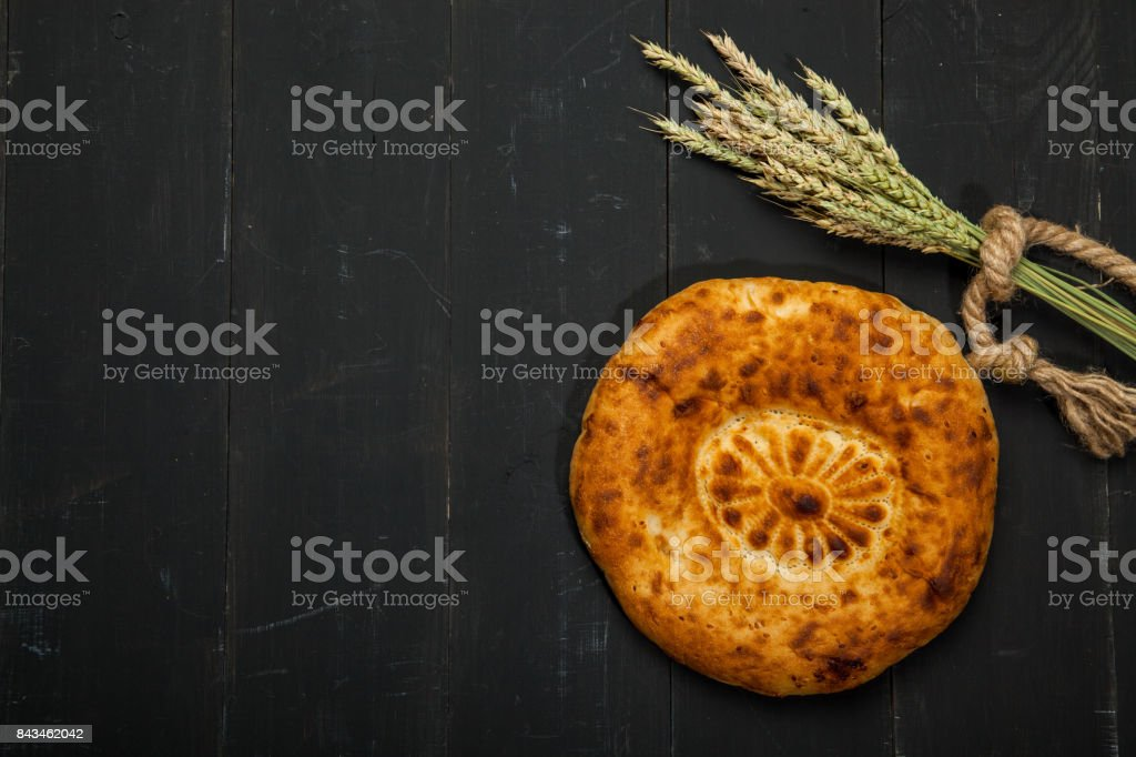 Wheat and flat cake on a black wooden background stock photo