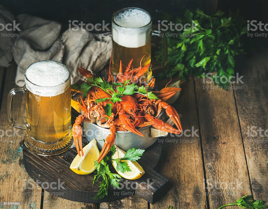 Wheat beer and boiled crayfish with lemon, fresh parsley stock photo