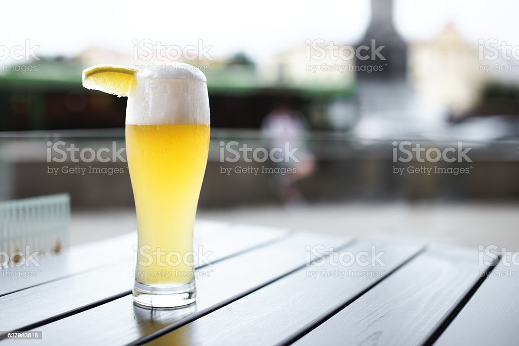 Wheat beer with slice of lemon on table stock photo