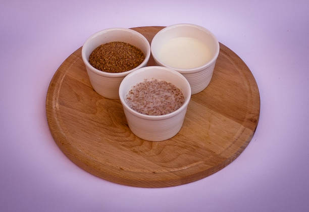 Wheat bran, yogurt and mix of them in white bowls on wooden plate stock photo