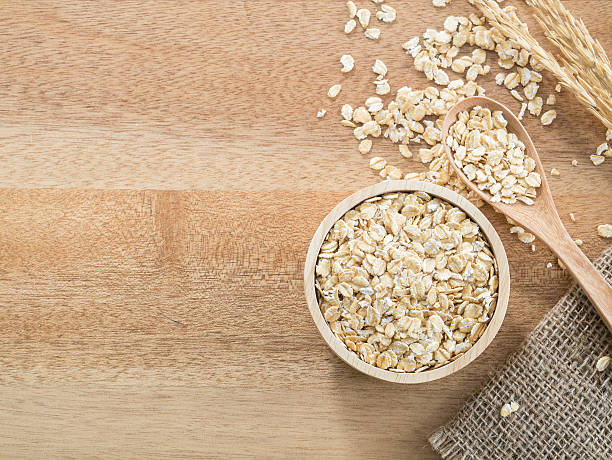 Wheat flakes in wooden bowl on wooden background stock photo