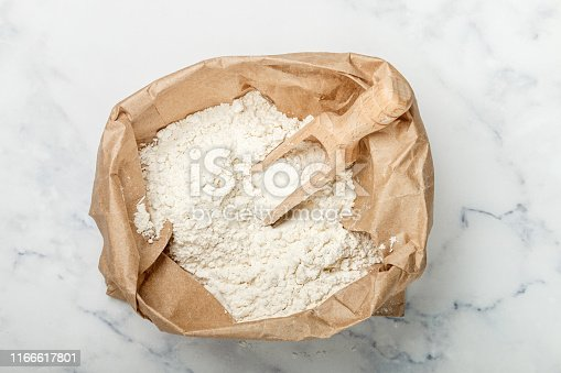 Wheat flour and a wooden scoop in a paper bag on a marble table. bakery concept. Selective focus