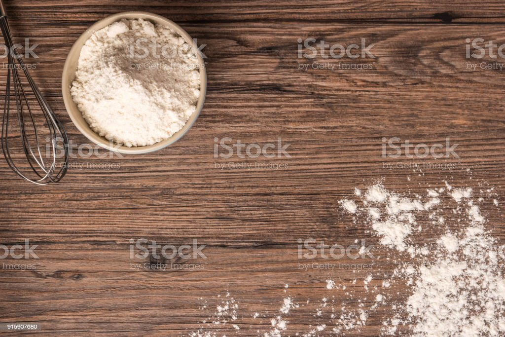 Wheat flour on a bowl on wooden background stock photo