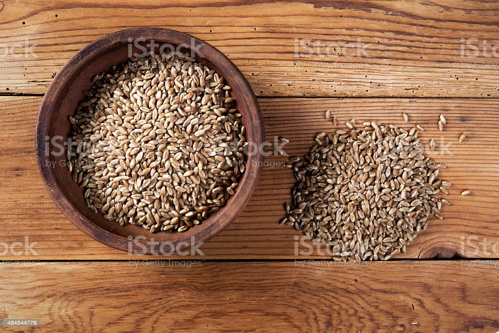 wheat grains and ceramic bowl on wooden table stock photo