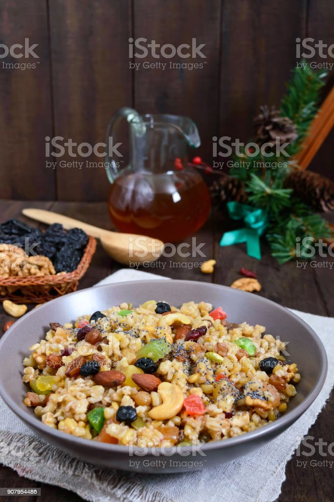 Wheat porridge with nuts, dried berries, raisins, poppies in a ceramic bowl on a dark wooden background. Proper nutrition. Healthy food. stock photo