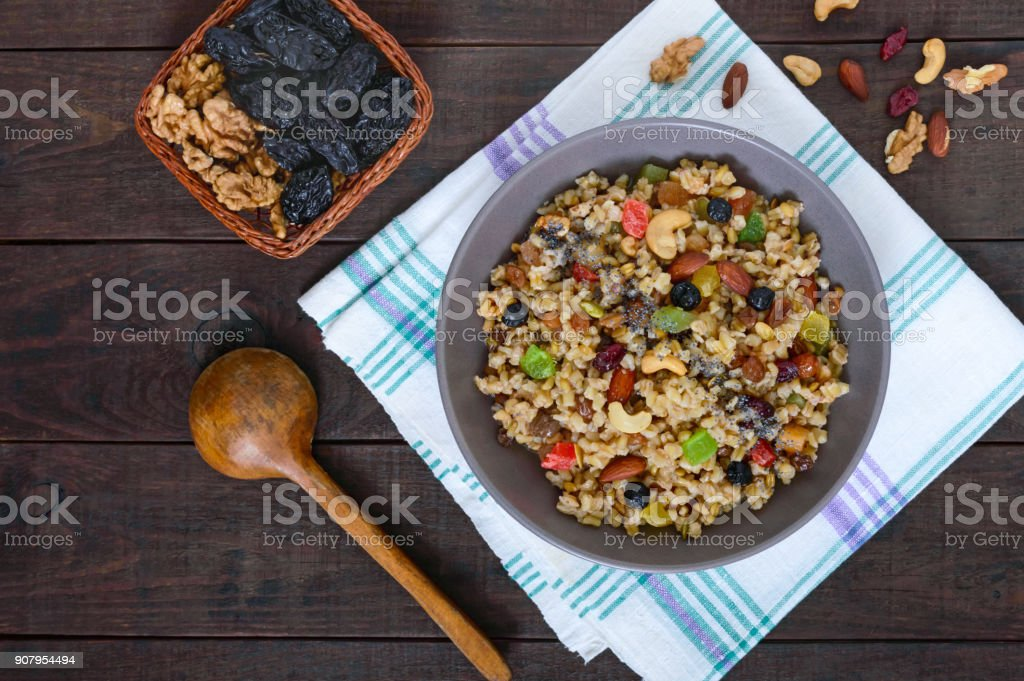 Wheat porridge with nuts, dried berries, raisins, poppies in a ceramic bowl on a dark wooden background. Proper nutrition. Healthy food. The top view stock photo