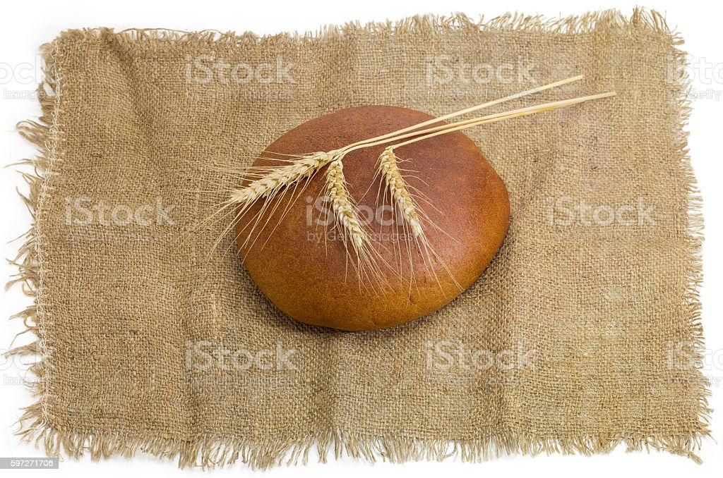 Wheat rye bread and three wheat spikes on a sackcloth royalty-free stock photo