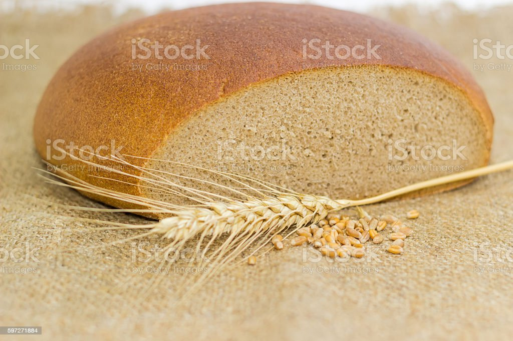 Wheat rye bread, wheat spike and handful of wheat grains royalty-free stock photo