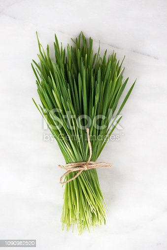 A bundle of wheatgrass on marble background.