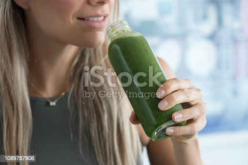 Unrecognizable woman is about to drink a green healthy smoothie.