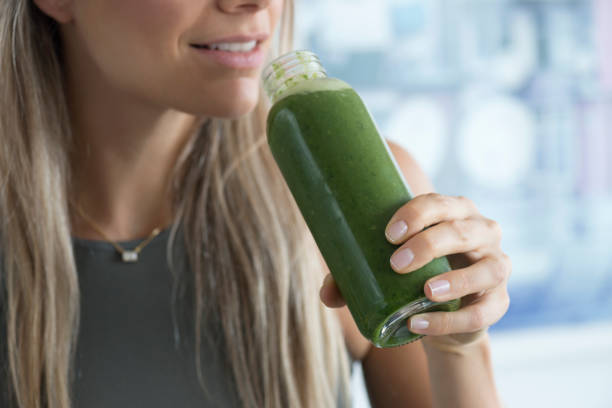 Wheatgrass Unrecognizable woman is about to drink a green healthy smoothie. anti inflammatory stock pictures, royalty-free photos & images