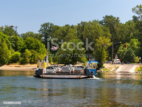 Wheatland, Oregon, USA - July 22, 2018: The Wheatland Ferry (Daniel Matheny V) carrying vehicles across the Willamette River. This cable ferry travels between Marion County and Yamhill County. Cars can be seen on the shore by the roads end waiting to take the ferry. This is also a popular area for people to enjoy the river on warm days. Salem, the state capital, is about 15 miles away.