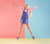 A cute little girl jumping against a colorful background