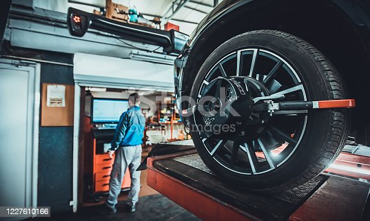 One man, mechanic in auto repair shop, wheel alignment equipment on a car wheel in a repair station.