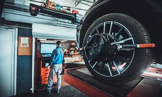 One man, mechanic in auto repair shop, wheel alignment equipment on a car wheel in a repair station.