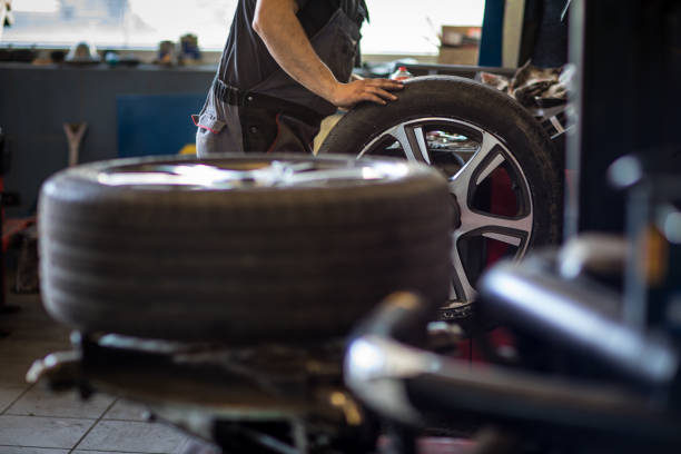 wielen balanceren of reparatie en wijzigen van auto band bij auto service garage - tyre stockfoto's en -beelden