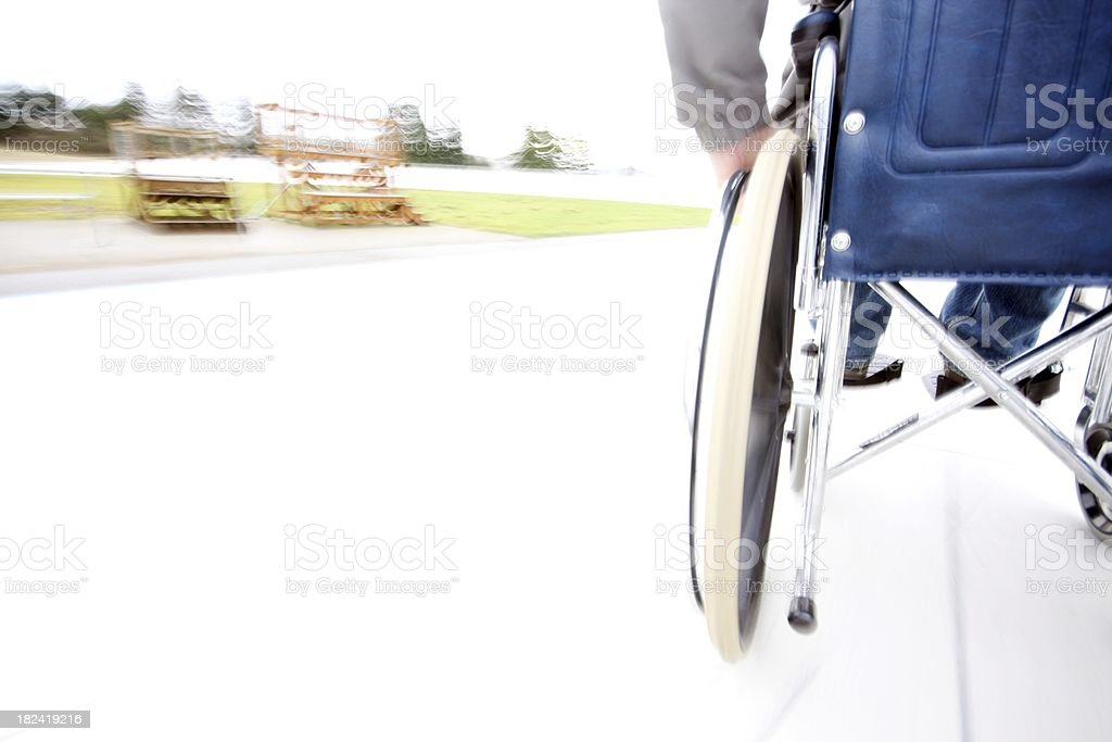 \'Trailing shot of a wheelchair user as the blurred track of a...