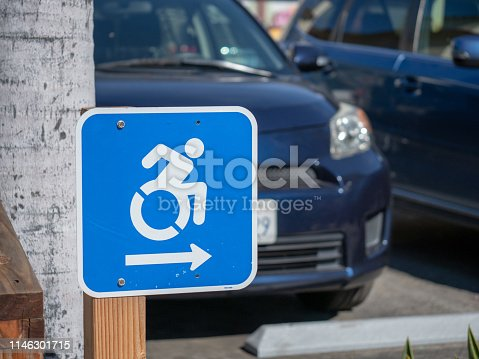 666724598istockphoto Wheel chair traffic sign pointing to the right in a parking lot 1146301715