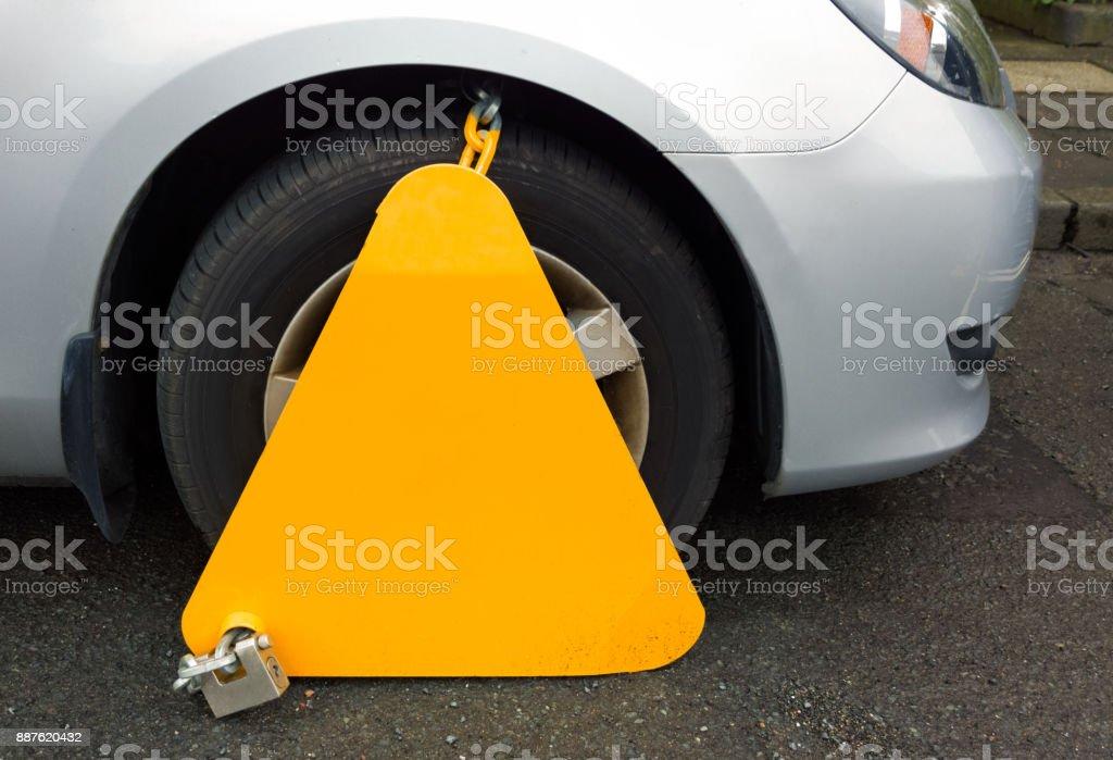 Wheel clamp locking car for parking infringement stock photo