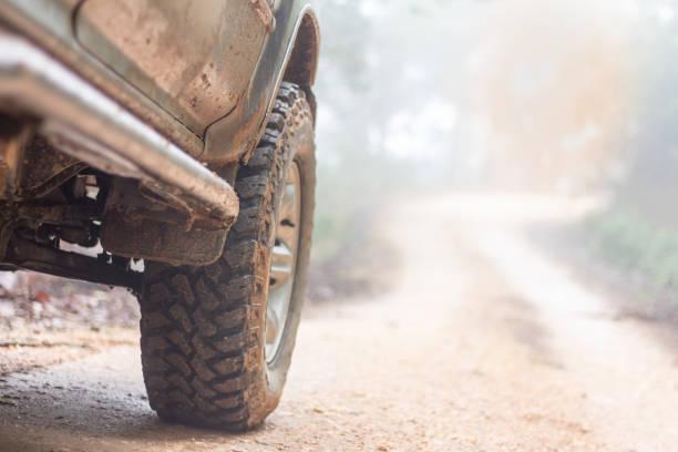 wiel close-up in een landschap van het platteland met een modderige weg, off-road reizen op bergweg, avontuurlijke reizen, regenseizoen. - tractieapparaat stockfoto's en -beelden