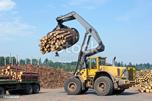 Wheel loader loading timber in saw mill. Grapple full of timber.