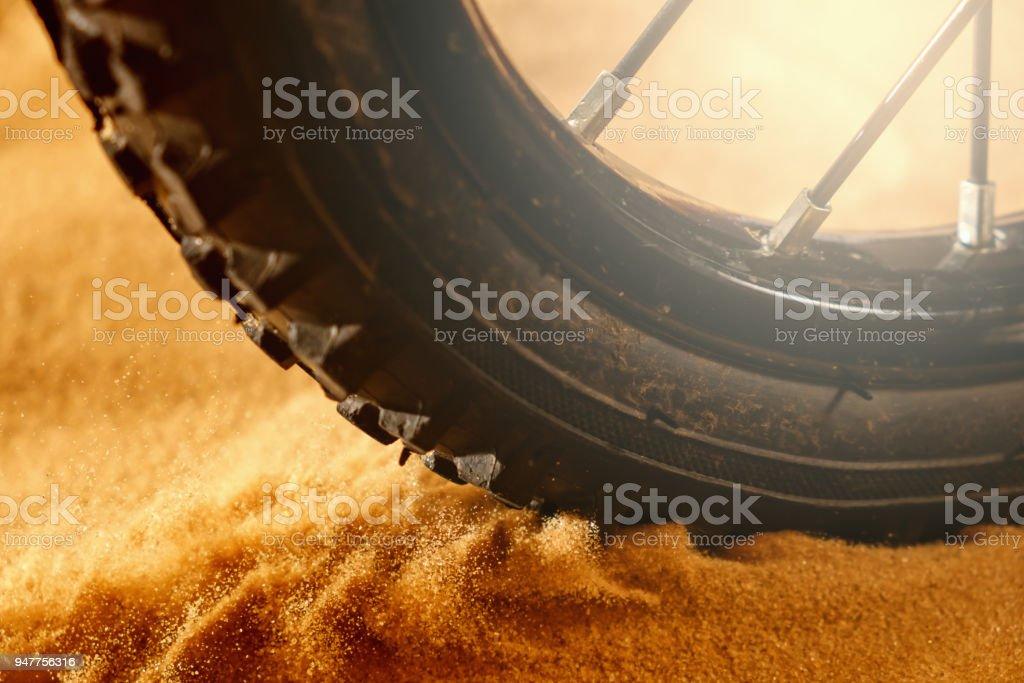Detalle de bicicleta rueda mountain bike en un día de sol y arena volando movimiento - foto de stock