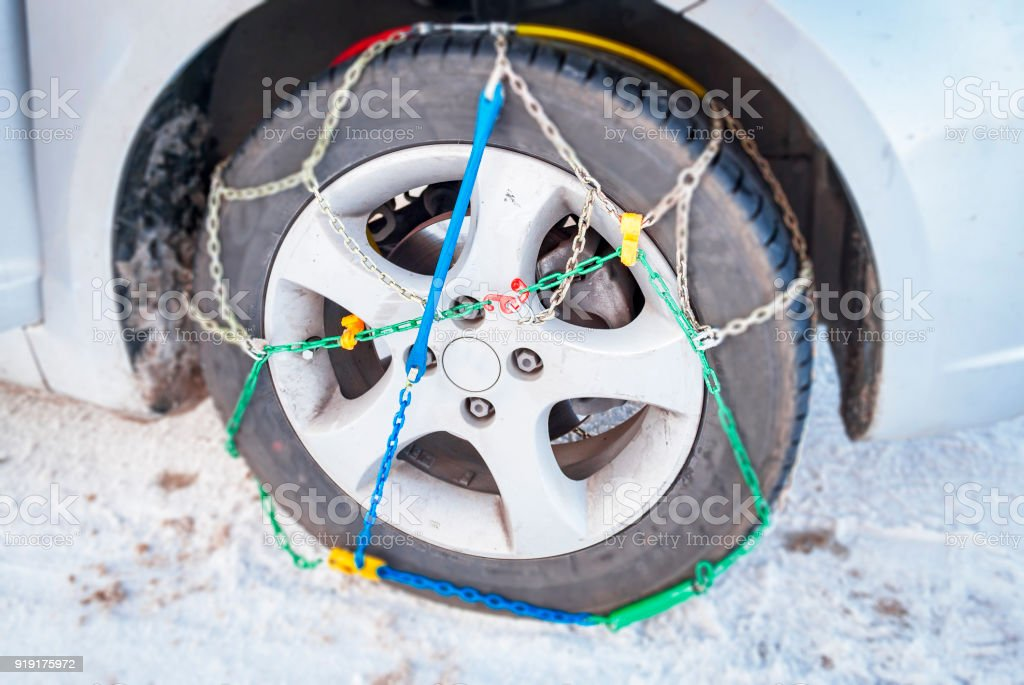 wheel of a car with mounted winter chains stock photo