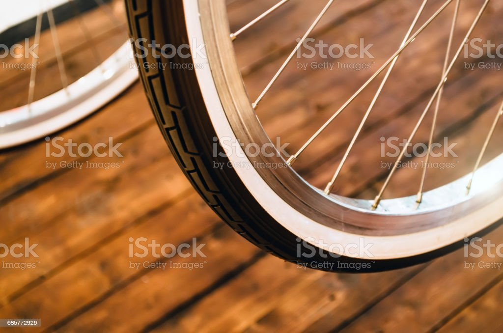 Wheel of a stylish bicycle with a white rim and a brown rubber tire on a stylish wooden background. royalty-free stock photo