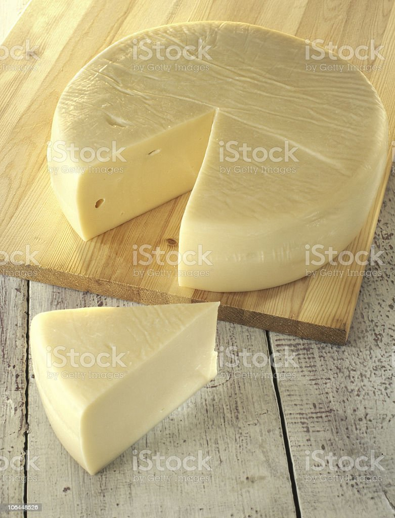 wheel of cheese on cutting board stock photo