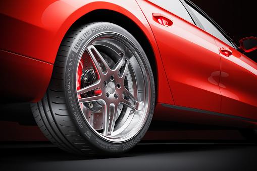 Wheel of red sports car closeup in studio lighting 3d render