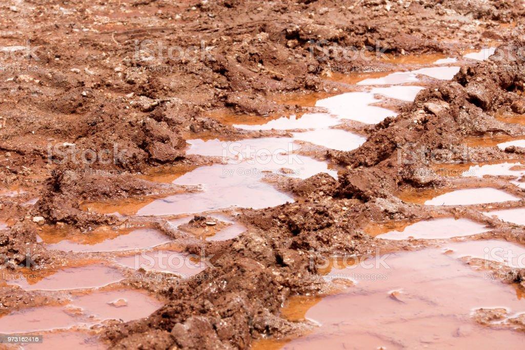 Rastreamento de roda na estrada, poça e lama depois da chuva. Vestígios no solo de trator, escavadeira, carro, marcas de pneu automotivo na trilha enlameada. Estrada de Sandy no país com poças d'água em dia de chuva. Fundo, textura. - foto de acervo