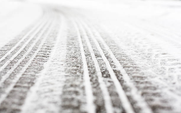 Wheel tracks on the road covered with snow Wheel tracks on the winter road covered with snow. tire track stock pictures, royalty-free photos & images
