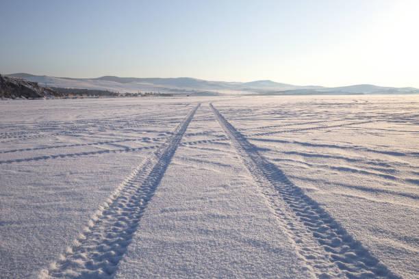 wielsporen op de winterweg bedekt met sneeuw. - tractieapparaat stockfoto's en -beelden