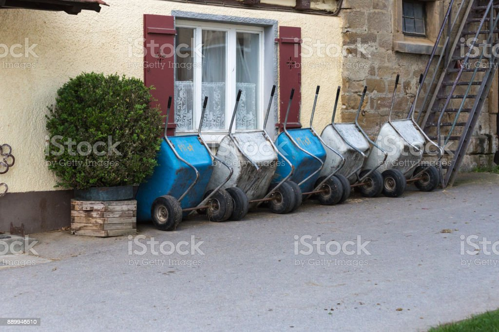 wheelbarrow of a stud farm at spring month may in south germany word mist means mist and futter means food stock photo