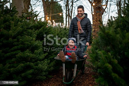 A Father giving his son a wheelbarrow ride at a Christmas market in Northeastern England. They are wearing warm clothing and having fun.