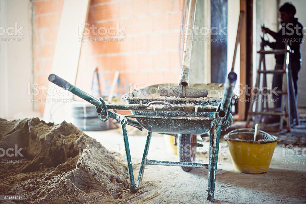 Wheelbarrow with cement in repairing apartment stock photo