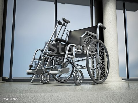 Wheelchair and crutches standing in front of hospital building.